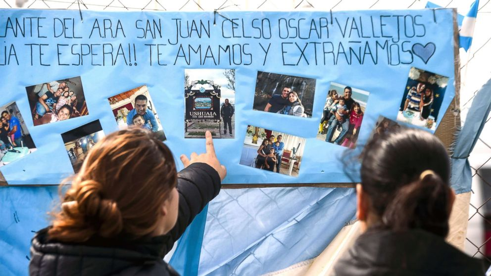 Women look at family pictures of missing Argentine submarine crew member Cesar Oscar Vallejos, hanging outside Argentina's Navy base in Mar del Plata, on the Atlantic coast south of Buenos Aires, on Nov. 24, 2017.