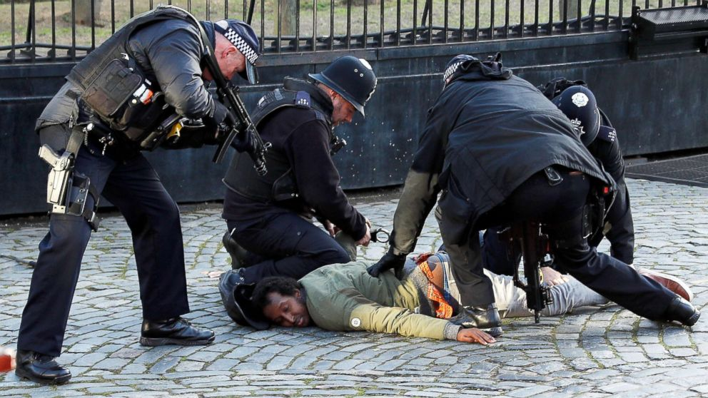 Armed police restrain a man inside the grounds of the Houses of Parliament in London, Dec. 11, 2018.