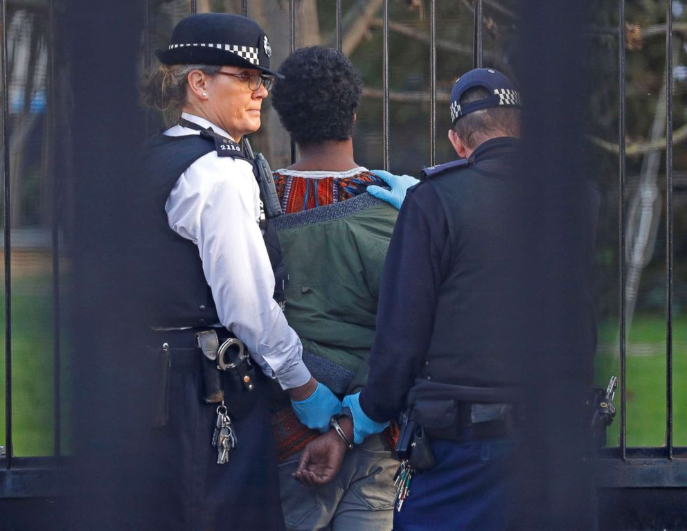 Police restrain a man inside the grounds of the Houses of Parliament in London, Dec. 11, 2018.