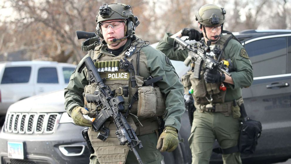 Police officers armed with rifles stage near a commercial building where an active shooter was reported in Aurora, Ill., Feb. 15, 2019.