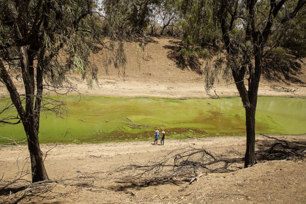 People stand on the banks of the Darling River, which is currently affected by extreme heat, drought and dust in Tilpa, Australia, Jan. 16, 2019.
