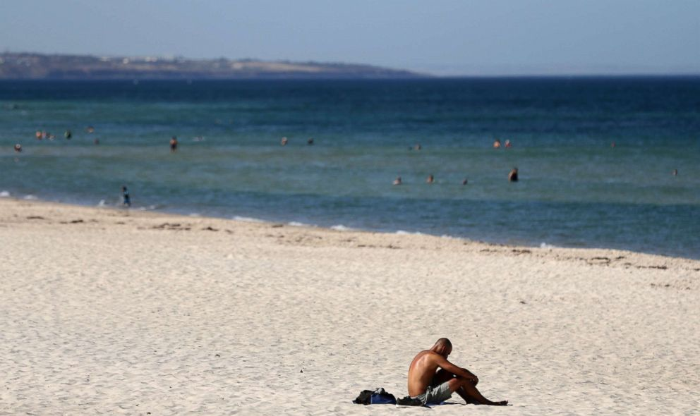 PHOTO: A beachgoer sits in the sun on Glenelg Beach in Adelaide, Australia, Jan. 24, 2019.
