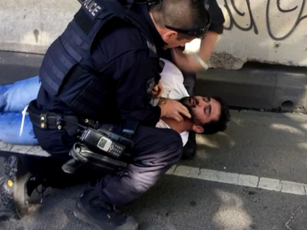 PHOTO: A police officer detains a man that was pulled from the car that rammed pedestrians at Flinders St station in Melbourne, Australia, Dec. 21, 2017.