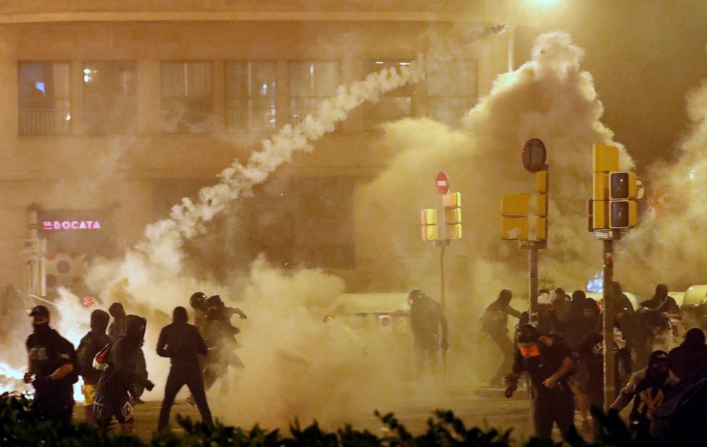 PHOTO: Catalan demonstrators throw back to the police a tear gas canister officer during Catalonias general strike, in Barcelona, Spain, October 18, 2019.
