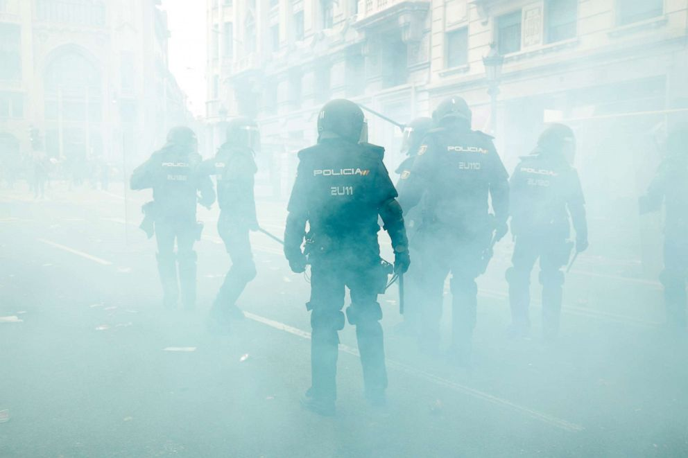 PHOTO: Spanish national police officers stand in the smoke as they protect the Police headquarters in Barcelona, on October 18, 2019, on the day that separatists have called a general strike and a mass rally.