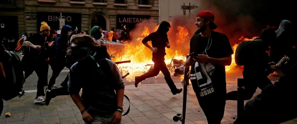 PHOTO: Protesters clash with police near the Police headquarters in Barcelona, on October 18, 2019, on the day that separatists have called a general strike and a mass rally.
