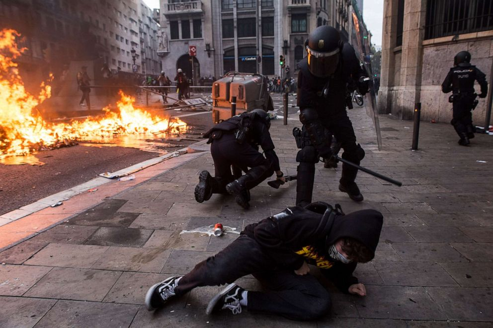 PHOTO: Police repeatedly hit a fallen protester. On the left a policeman fallen on the ground when charging against the protesters, in Barcelona, Spain, on October 18, 2019.