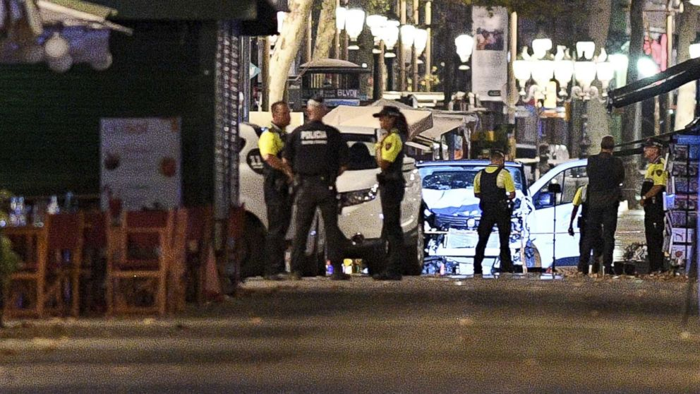 A damaged van, believed to be the one used in the attack, is surrounded by police officers in the Las Ramblas area, Aug. 17, 2017 in Barcelona, Spain.
