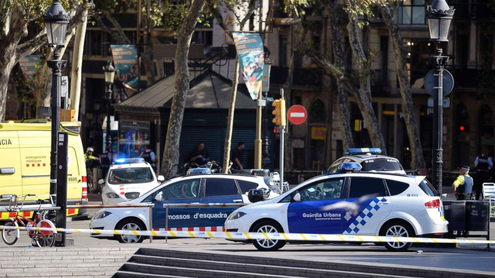 Policemen stand next to vehicles in a cordoned off area after a van ploughed into the crowd, injuring several persons on the Rambla in Barcelona, Aug. 17, 2017.