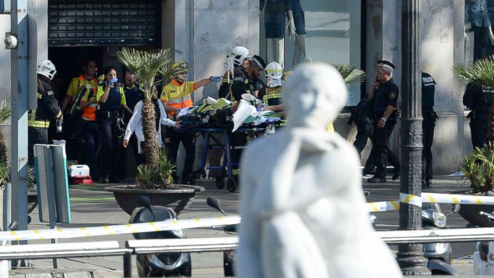 A person is stretched out of a mall by medical staff members in a cordoned off area after a van ploughed into the crowd, injuring several persons on the Rambla in Barcelona, Aug. 17, 2017.