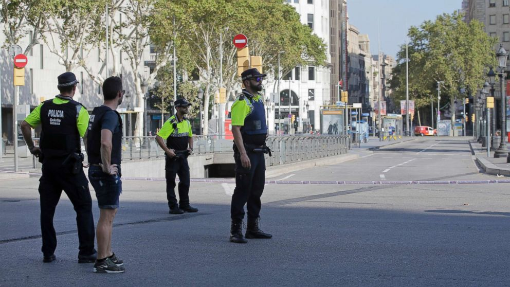 Police officers cordon off a street in Barcelona, Aug. 17, 2017. Police in the northern Spanish city of Barcelona say a white van has jumped the sidewalk in the city's historic Las Ramblas district, injuring several people.