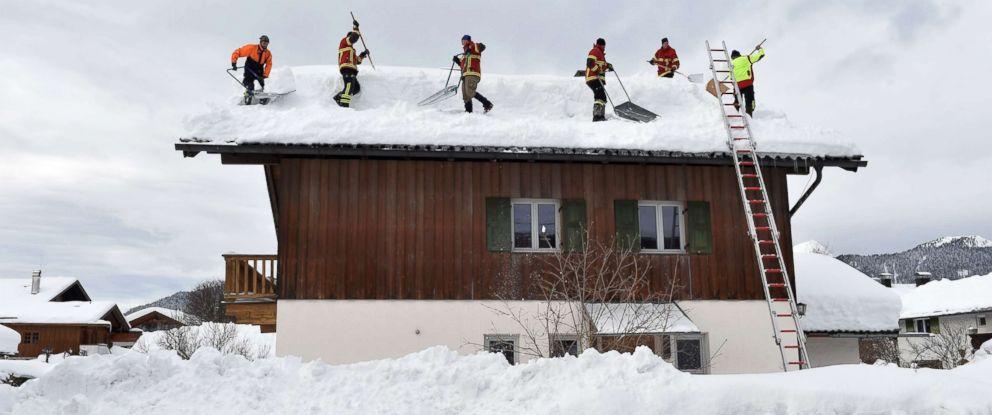 PHOTO: Firefighter helpers remove snow from a rooftop in the small Bavarian village of Kruen near Garmisch-Partenkirchen, Germany, Jan. 15, 2019.