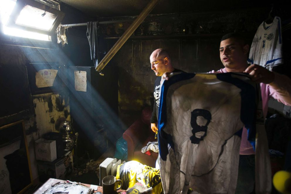 PHOTO: An employee of Beitar Jerusalem holds up a shirt that was damaged along with other items in a suspected arson attack at the soccer teams club house in Jerusalem, Feb. 8, 2013.