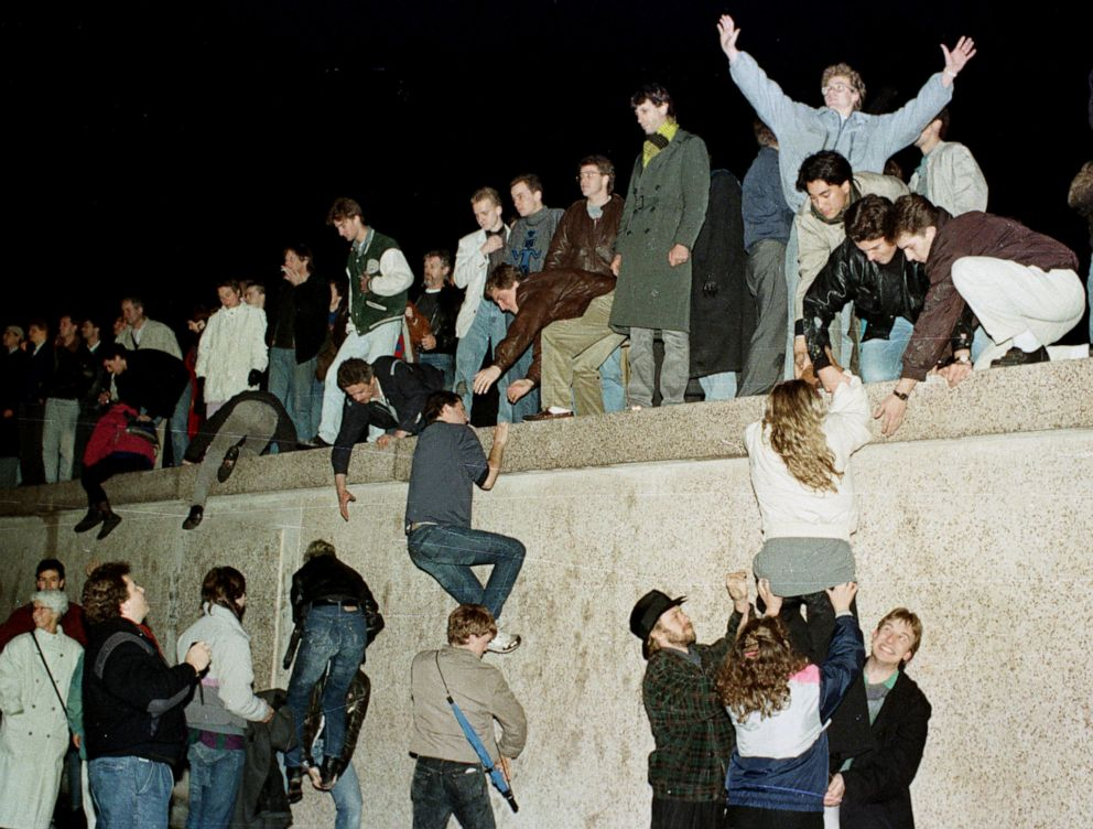 PHOTO: In this Nov. 9, 1989, file photo, East and West German citizens celebrate as they climb the Berlin wall at the Brandenburg gate after the opening of the East German border was announced in Berlin, Germany.