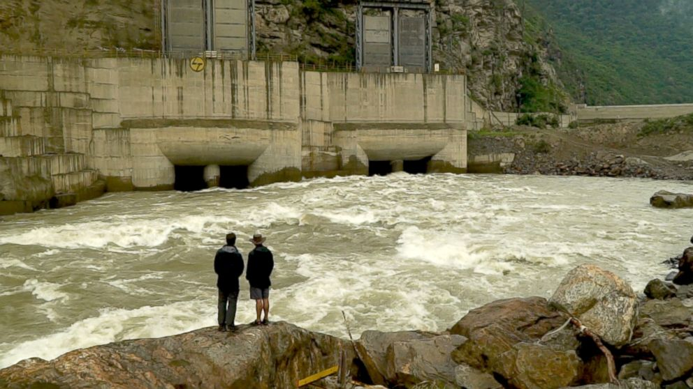 PHOTO: Bob Woodruff and River guide Sonam Toby Tobgay stand in front of the still-under-construction Punatsangchhu-1 Hydropower Project.