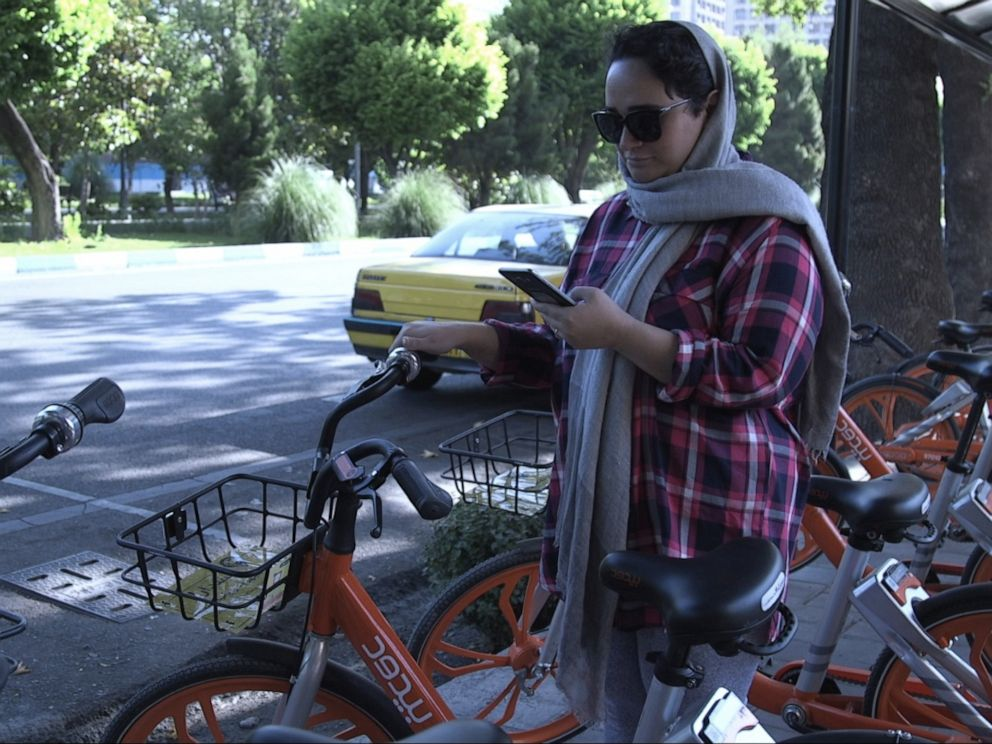 PHOTO: Saba Javid tries to open one of the Bdood bicycle using the application on her phone in Tehran, Iran, on Friday, June 14, 2019.
