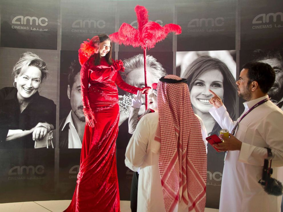 PHOTO: Visitors chat with an actress in front of posters of Hollywood stars during invitation-only screening, at the King Abdullah Financial District Theater, in Riyadh, Saudi Arabia, April 18, 2018.