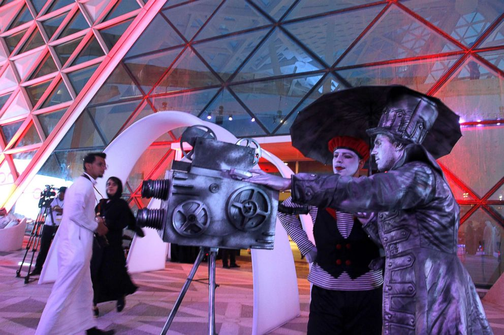 Two men in costume welcome visitors during the opening of the AMC Entertainment cinema theatre at the King Abdullah Financial District in Riyadh, Saudi Arabia, April 18, 2018.