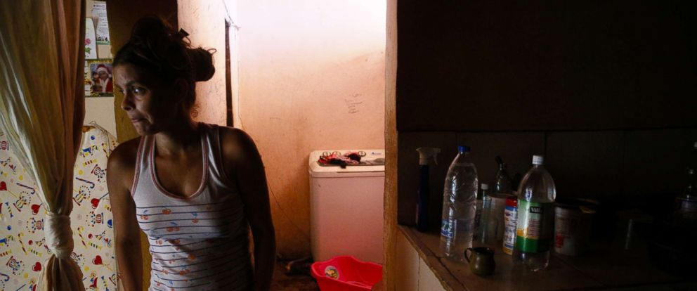 A woman looks on at her home during blackouts, which affects the water pumps, March 12, 2019, in Caracas, Venezuela.