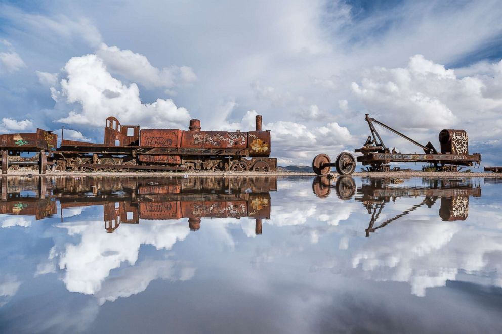 PHOTO: Clouds are perfectly reflected in the clear salt flats while a rusted train rests atop the vast flat in Salar de Uyuni, Bolivia, Jan. 31, 2014.