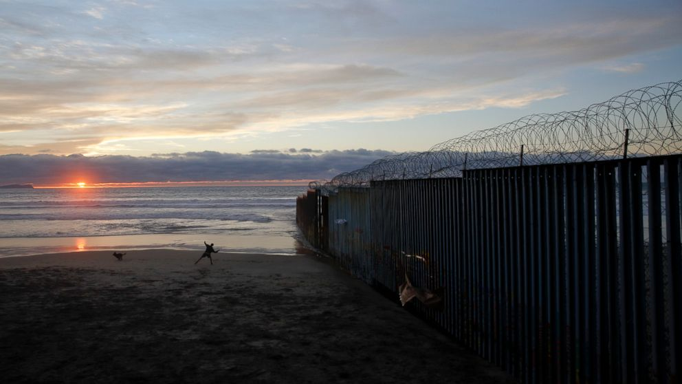 In this Jan. 9, 2019, file photo, a man throws a ball for his dog next to the border wall topped with razor wire in Tijuana, Mexico.