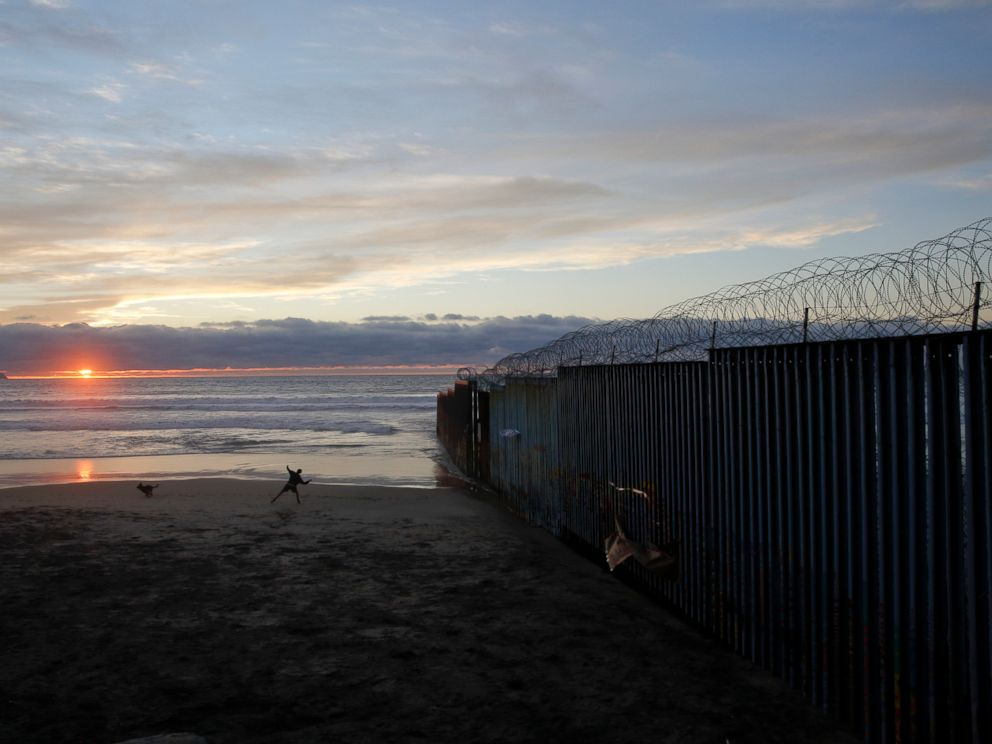 PHOTO: In this Jan. 9, 2019, file photo, a man throws a ball for his dog next to the border wall topped with razor wire in Tijuana, Mexico.