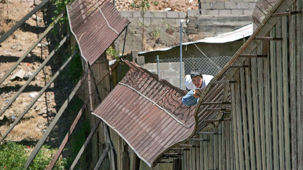 In this May 31, 2006, file photo, a man climbs over the international border into Nogales, Ariz., from Nogales, Mexico.