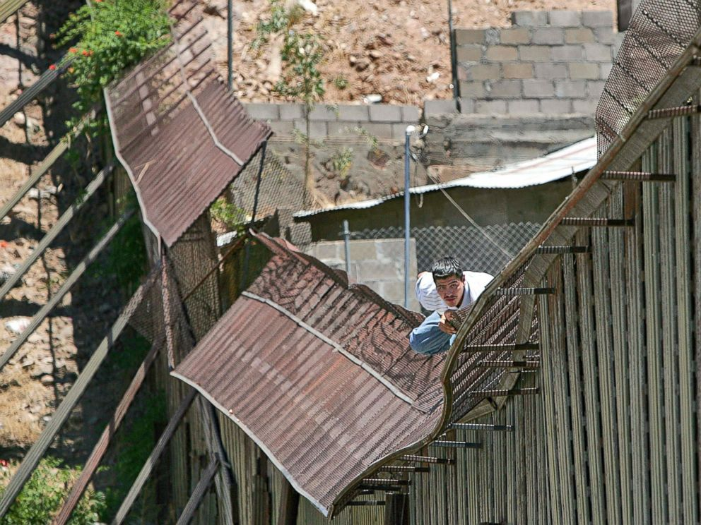 PHOTO: In this May 31, 2006, file photo, a man climbs over the international border into Nogales, Ariz., from Nogales, Mexico.