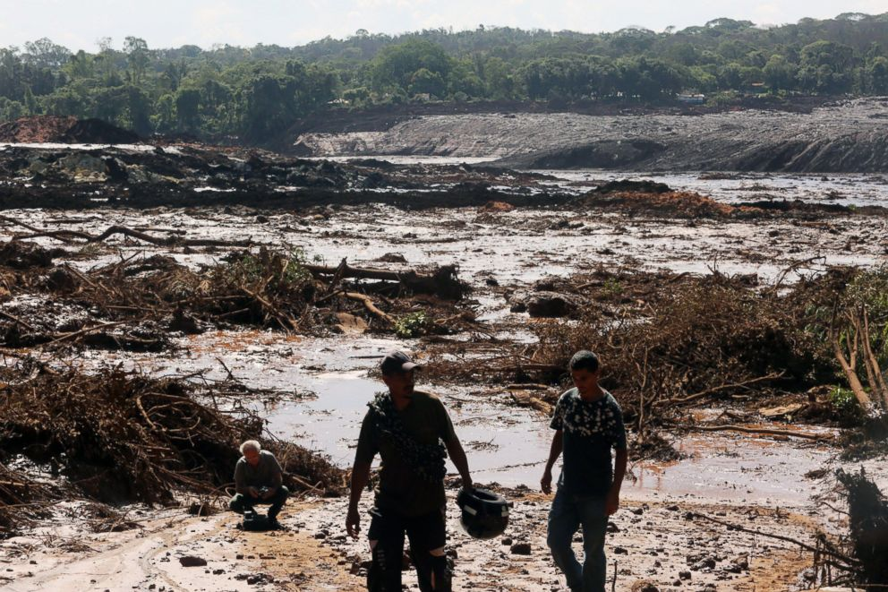 PHOTO: Men walk near damage caused by the breakage of a dam containing mineral waste from Vale, the worlds largest iron producer, in Brumadinho, municipality of Minas Gerais, Brazil, Jan. 25, 2019.