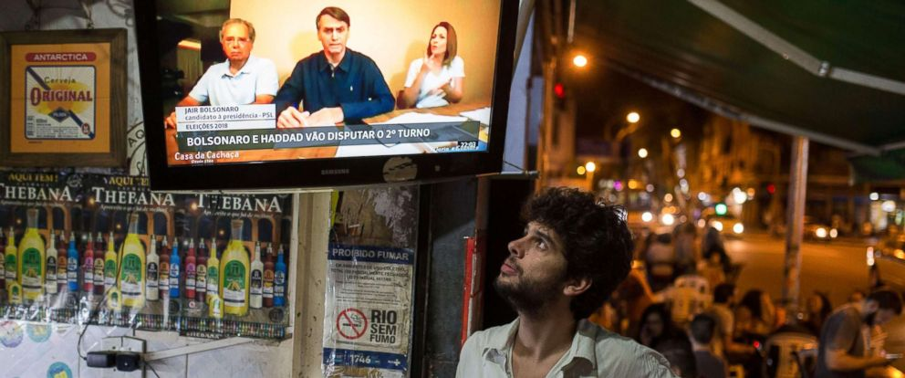 PHOTO: People watch an internet video of Brazilian presidential candidate for the Social Liberal Party (PSL), Jair Bolsonaro, on TV at a bar of Lapa neighborhood, in Rio de Janeiro, Oct. 07, 2018.