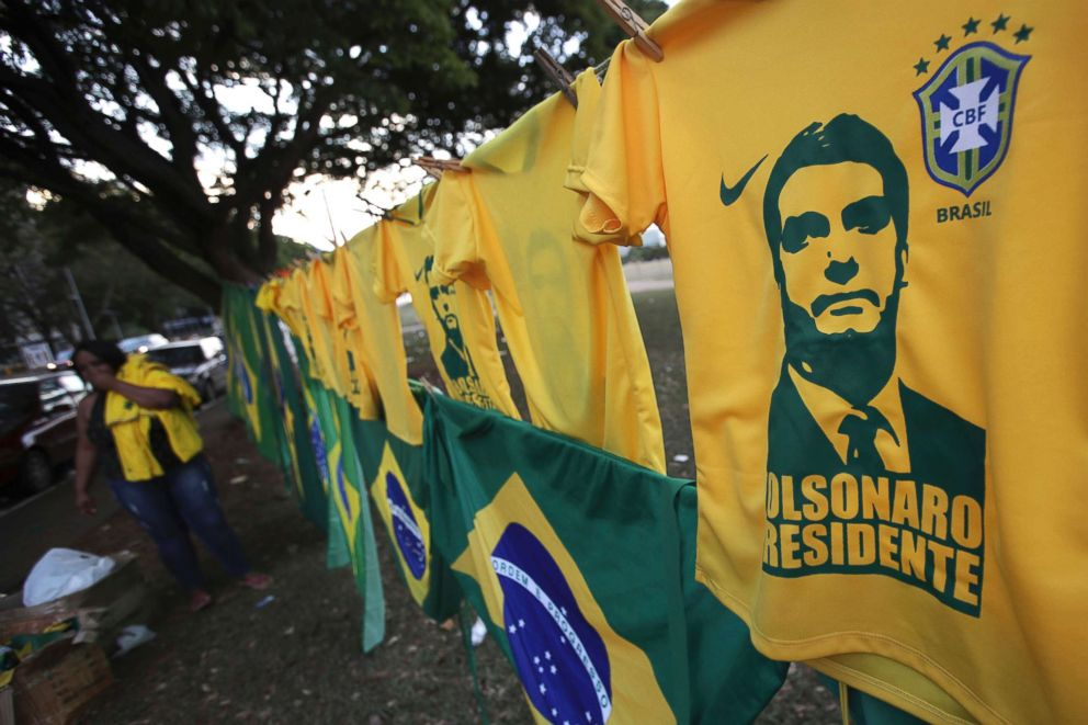 PHOTO: A woman sells T-shirts and flags with the image of presidential frontrunner Jair Bolsonaro of the Social Liberal Party, in front of the headquarters of the national congress, in Brasilia, Brazil, Oct. 7, 2018.