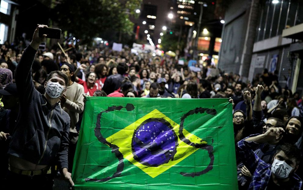 PHOTO: Protesters hold a Brazilian flag with the letters SOS written on it during a demonstration to demand for more protection for the Amazon rainforest, in Sao Paulo, Brazil, on Friday, Aug. 23, 2019.