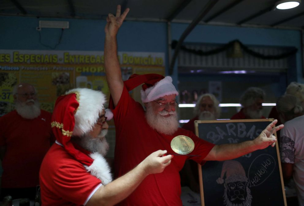 "Carlos Alberto Patricio, a student of the Brazil's school of Santa Claus, receives his trophy during a ritual named ""Barbas de Molho"" to mark the end of Christmas season, in Rio de Janeiro, Dec. 26, 2018."