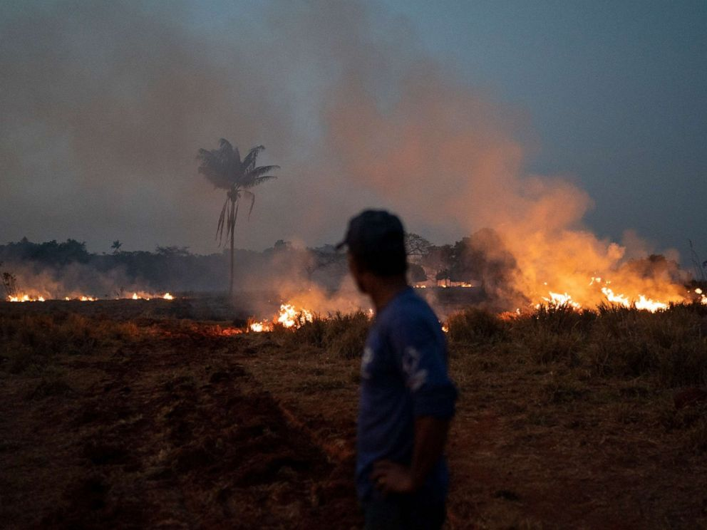 PHOTO: Neri dos Santos Silva watches an encroaching fire threat after digging trenches to keep the flames from spreading to the farm he works on, in the Nova Santa Helena municipality, in the state of Mato Grosso, Brazil, Friday, Aug. 23, 2019.