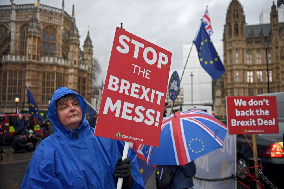 PHOTO: Brexit protesters shelter from a rain shower outside the houses of parliament in London, Jan. 16, 2019.