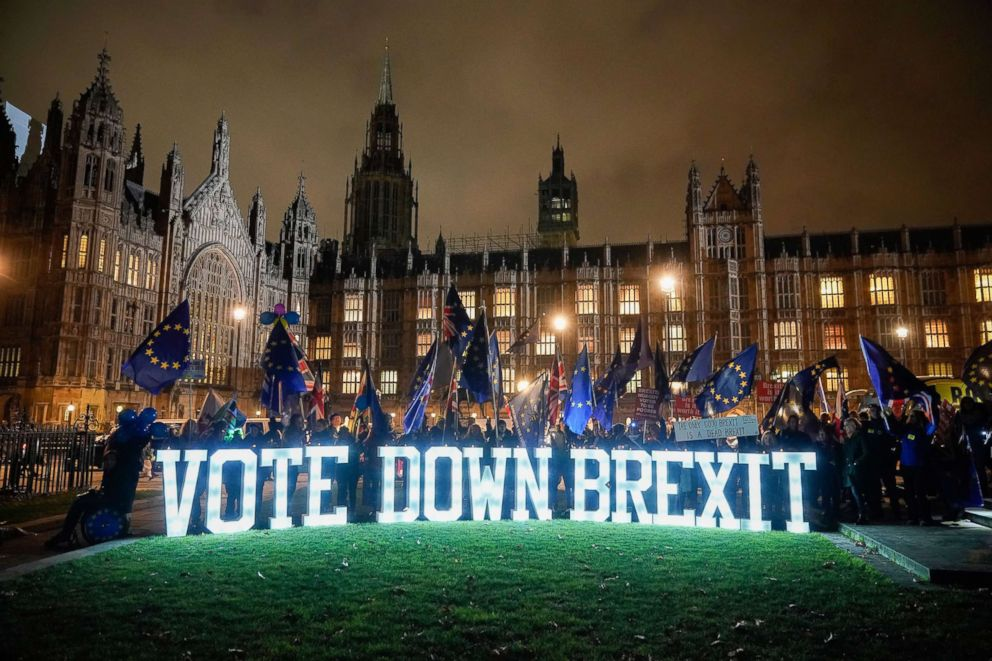 Anti-Brexit protesters use illuminated signs as they demonstrate with placards outside the Houses of Parliament, Westminster on Dec. 10, 2018 in London.