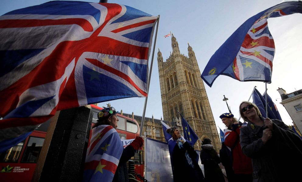 PHOTO: Anti-brexit campaigners wave Union and EU flags outside the Houses of Parliament in central London on Dec. 17, 2018, ahead of a statement by Britains Prime Minister Theresa May.
