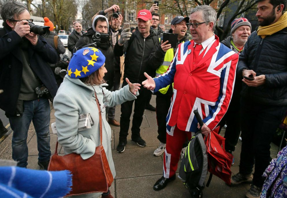 PHOTO: An anti-Brexit, left, and pro-Brexit supporter debate outside the House of Parliament in London, March 12, 2019.
