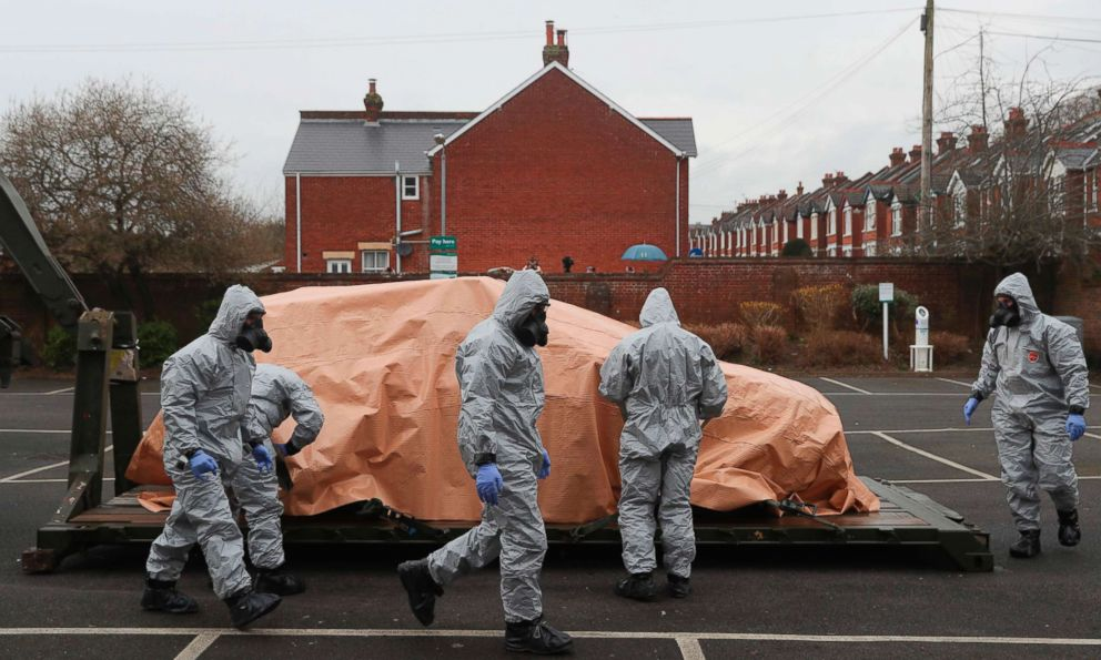 PHOTO: Military personnel wearing protective coveralls load a police car onto a military vehicle for it to be taken away from a cordoned off area behind a police station in Salisbury, England, on March 11, 2018.
