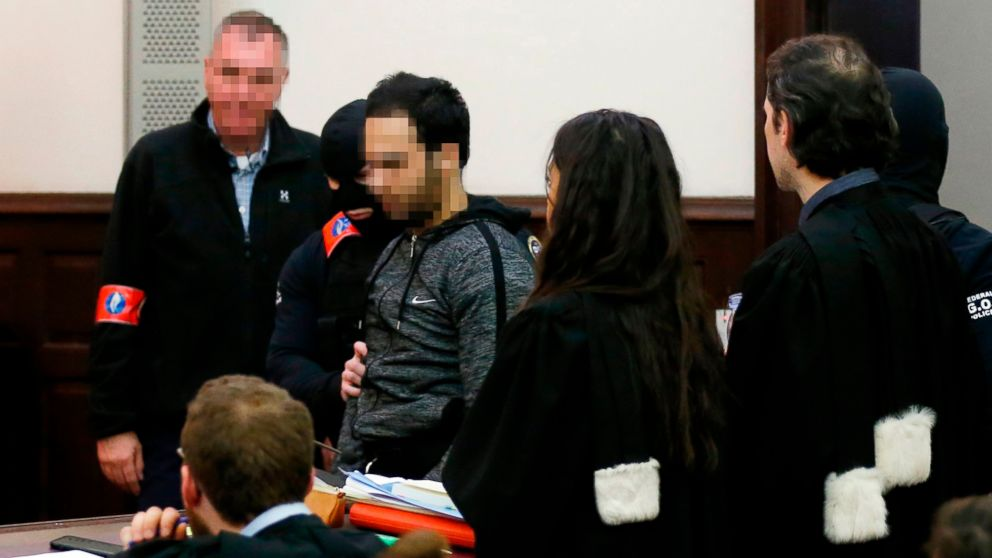 The alleged accomplice of the November 2015 Paris attacks suspect Salah Abdeslam, Sofiane Ayari, center, is escorted by Belgian police officers as he arrives in a courtroom in Brussels on Feb. 8, 2018.
