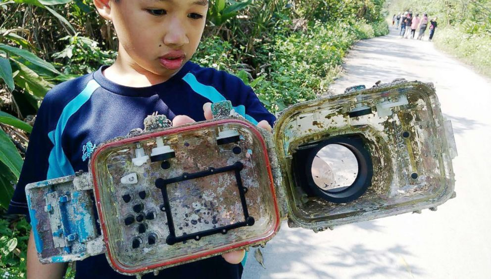 PHOTO: A school pupil displays the barnacle-covered water-proof camera casing which washed up on a beach.