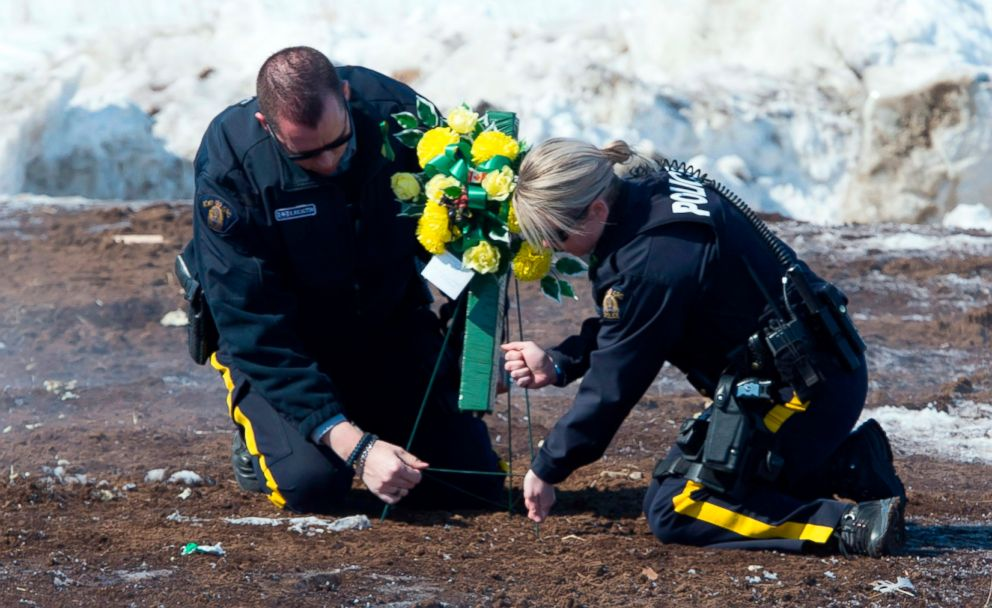 PHOTO: Members of the Royal Canadian Mounted Police lay flowers at the intersection of a crash site near Tisdale, Saskatchewan, April, 8, 2018.