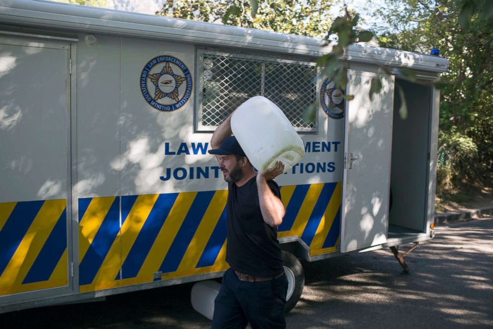 PHOTO: A man carrying a container of water passes a police trailer parked outside a source for natural spring water in Cape Town, Feb. 1, 2018.