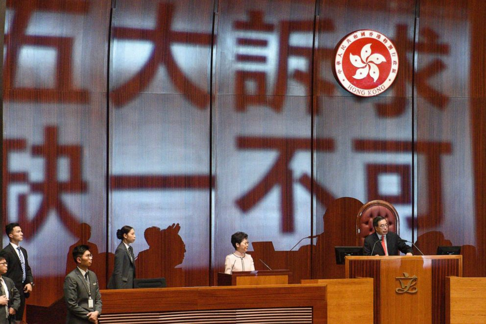 PHOTO: The words Five demands, not one less are projected onto the wall behind Hong Kongs Chief Executive Carrie Lam (2-R) as she arrives to deliver her annual policy address at the Legislative Council in Hong Kong on Oct. 16, 2019.