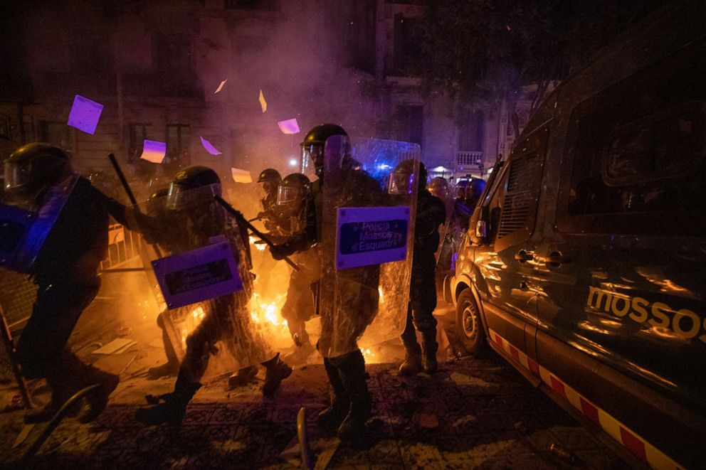 PHOTO: Policemen in riot gear move past a burning barricade during clashes with demonstrators in Barcelona, Oct. 15, 2019.