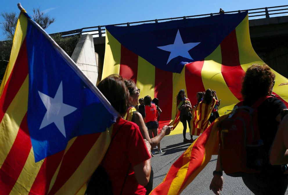 PHOTO: Demonstrators hold Catalan pro-independence Estelada flags as they march on the Nacional 2 road in Sils, near Girona, Oct. 16, 2019, a day after police arrested 51 people across Catalonia.
