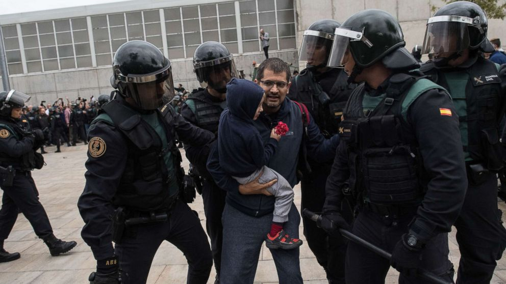 A man and a child holding a red flower run from the police as they move in on the crowds, as members of the public gather outside, to prevent them from stopping the opening and the intended voting in the referendum at a polling station where the Catalonia President Carles Puigdemont will vote later today, Oct. 1, 2017 in Sant Julia de Ramis, Spain.