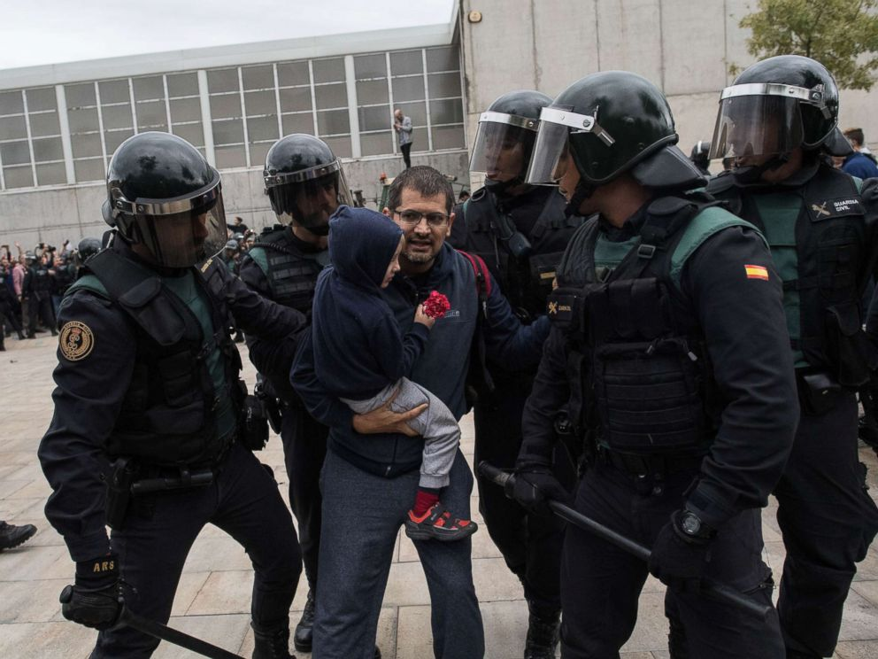 PHOTO: A man and a child holding a red flower run from the police as they move in on the crowds, Oct. 1, 2017 in Sant Julia de Ramis, Spain.