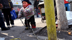 PHOTO A young boy is chained to a post in China.