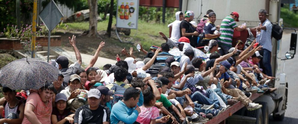 PHOTO: Honduran migrants who are traveling to the United States as a group, get a free ride in the back of a trailer truck flatbed, as they make their way through Teculutan, Guatemala, Oct. 17, 2018.